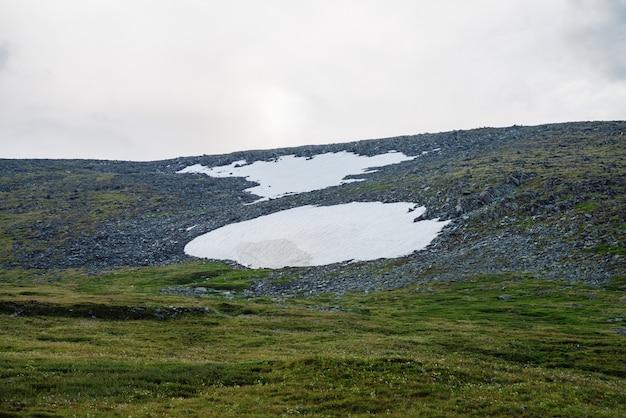 峠の雪原とミニマルな高原の風景。山腹に雪がある最小限の高山の風景。雪の丘の中腹。雪の斜面への大気の眺め。高地の雄大な自然。