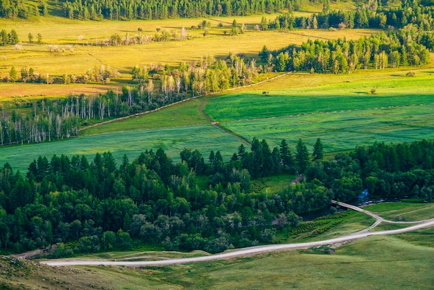 日光の下で農業分野に空中の風光明媚なビュー。フィールド、森、山川、橋、未舗装の道路、日没時のフェンスと田舎の鮮やかな風景。夕方の光の中で美しい国の土地。