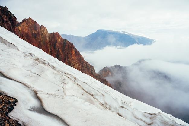 Вид сверху на ледяной карниз над пропастью. горный скалистый пик над облаками. атмосферный альпийский пейзаж с низкими облаками в пропасти среди больших гор. прекрасные горные пейзажи с ледниковой вершиной.