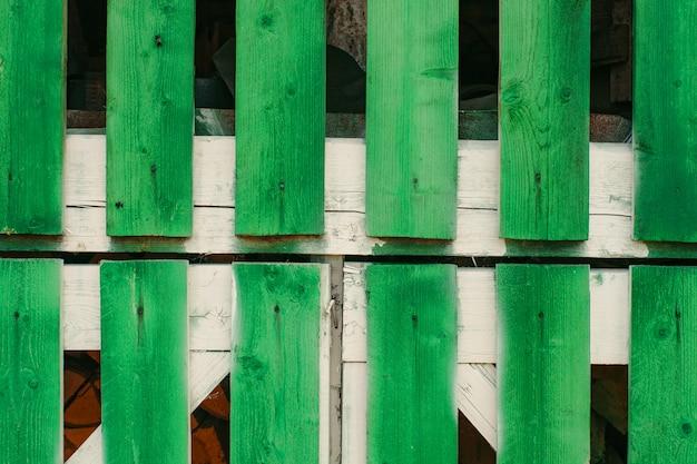 鮮やかな緑の長い板からの納屋の門の断片がクローズアップします。コピースペース付きの木製ドアの後ろの小屋に薪を保管。素朴な生き方。グランジ建設の詳細な背景をテクスチャ。