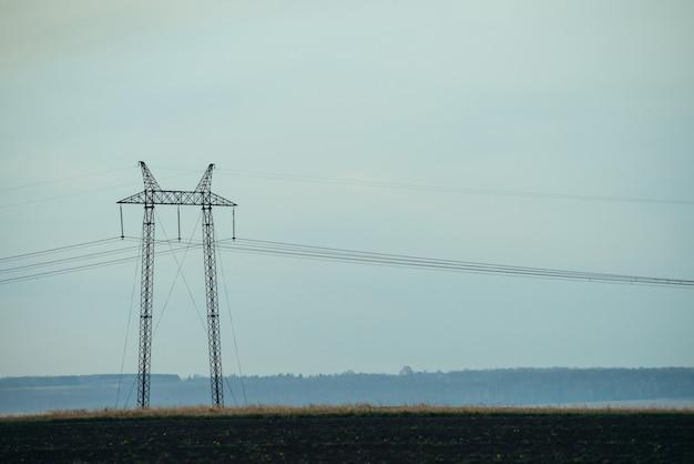 青空のクローズアップの背景の送電線。コピースペースを持つ電柱のシルエット。地上の高電圧のワイヤー。電気業界。