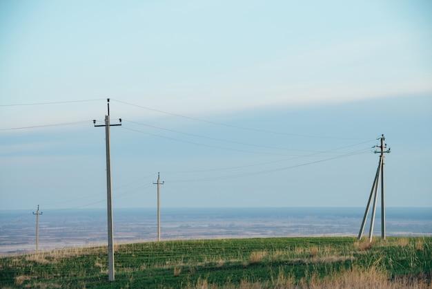 青い空の下で緑の野原で電力線のある大気の風景。コピースペースを持つ電気柱の背景画像。地上の高電圧のワイヤー。電気業界。