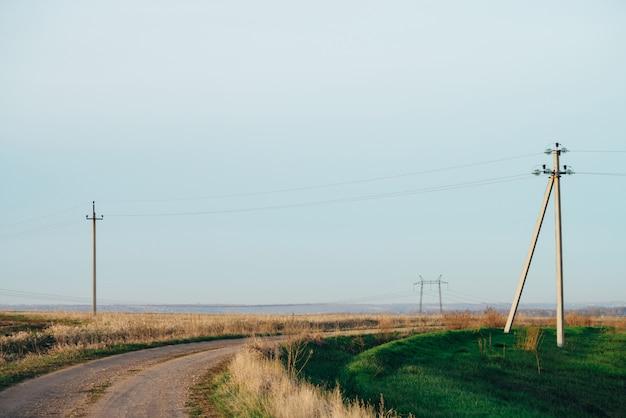 青い空の下の未舗装の道路と緑のフィールドに電力線のある大気の風景。コピースペースを持つ電気柱の背景画像。地上の高電圧のワイヤー。電気業界。