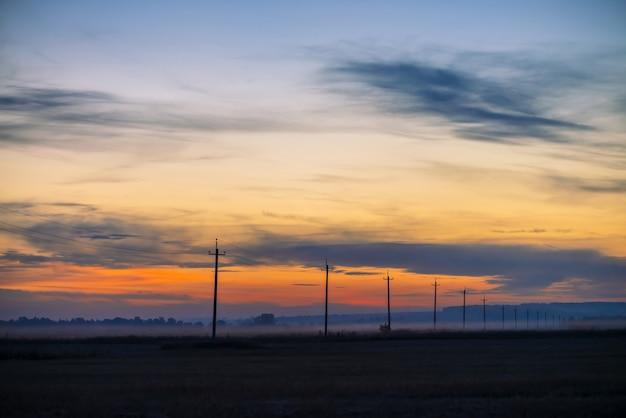 Линии электропередач в поле на рассвете