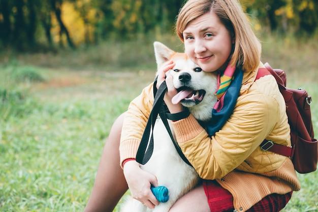 秋の色の女の子と遊ぶ美しいジンジャーハスキー犬。女性とフォクシー犬のクローズアップの肖像画を感じています。少女は、新鮮な空気の公園で白い赤いハスキーで遊ぶ。屋外で飼い主と一緒にペットを散歩。