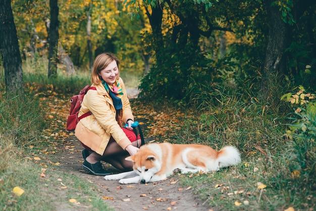 公園で女の子と遊ぶ若い赤いハスキー犬。美しい女性と紅葉のフォクシー犬。少女は新鮮な空気で白いジンジャーハスキーを果たしています。飼い主と一緒に屋外でペットを散歩。カラフルな秋のシーン