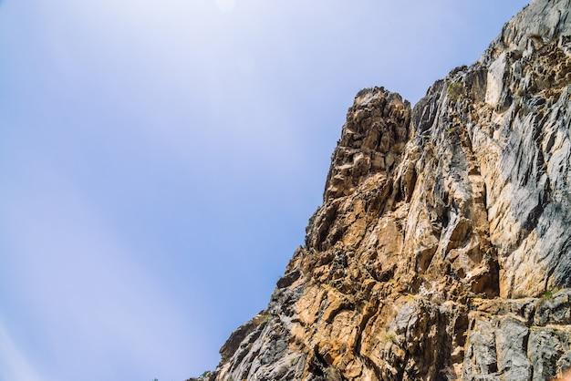 曇り空のクローズアップの下で大きな山の崖。