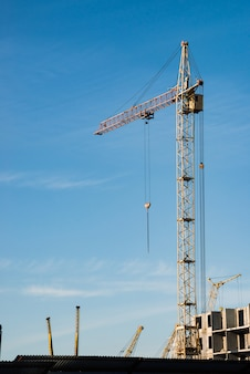 青い空を背景に建設中の建物の上の大きなタワークレーン。