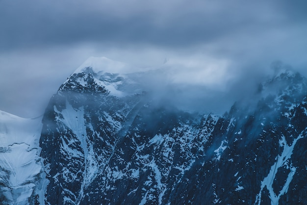 夕暮れの曇り空に雪と大きな山の頂上。