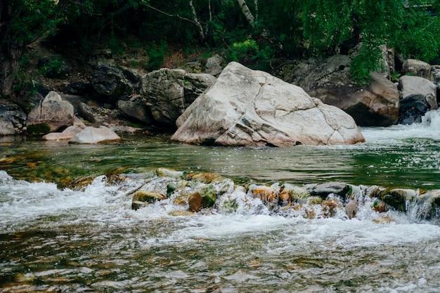 Живописный пейзаж с красивым горным ручьем с зеленой водой среди пышных зарослей.