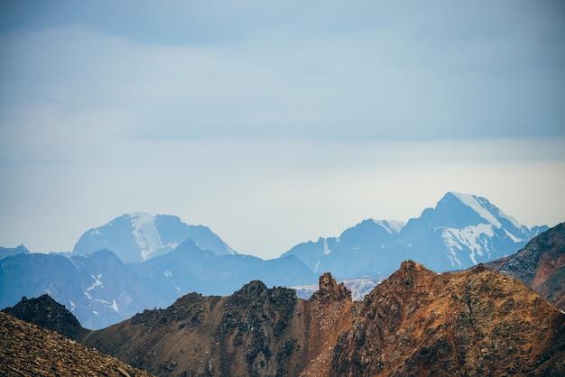 Золотые скалистые горы и гигантский заснеженный горный хребет.