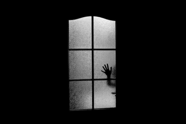 ガラスのドアの後ろに手の暗いシルエット