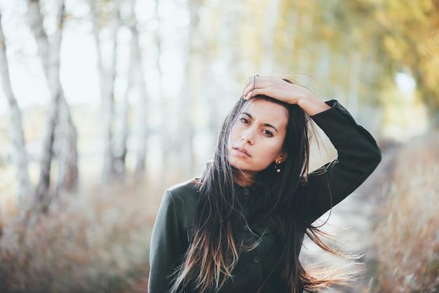 Красивая девушка с длинными черными волосами в парке