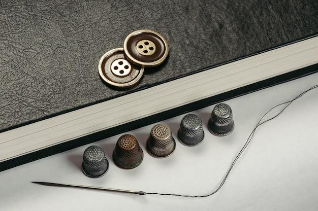 本の金色のボタン。本のページの背景に古い指ぬきと針と糸。