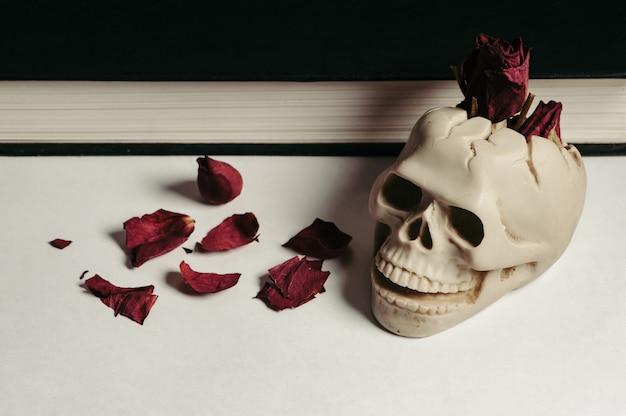赤い乾燥されたばらと白い背景の上のビンテージスカル灰皿。設計。本。