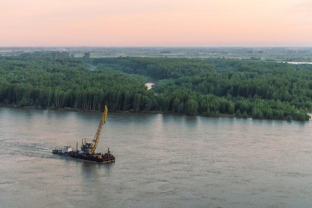 緑の海岸とコピースペースが付いている船の美しい川の風景