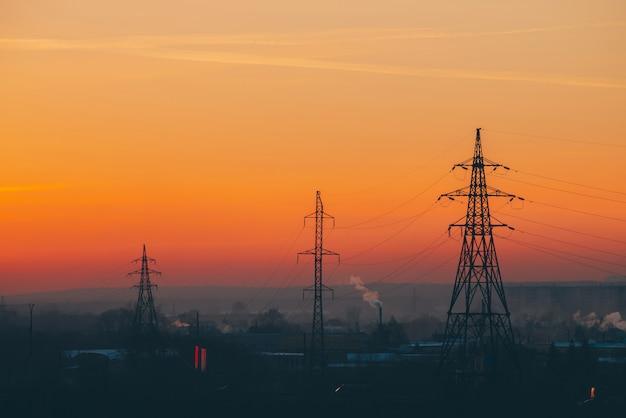 夜明けの都市の送電線