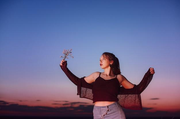 Рыжеволосая девушка стоит на краю пропасти на закате.