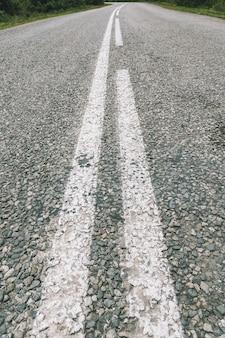 Шоссе из крошечного асфальтового гравия, неровной асфальтовой дороги из зернистых камней с белой дорожной разметкой в перспективе