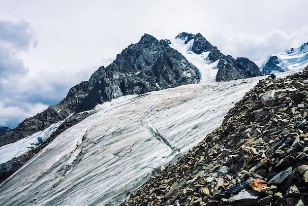 巨大な山の尾根に雪が降る