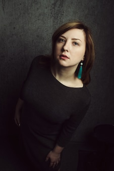 灰色のシーンにターコイズピアスと美しいスタイリッシュな女の子のヴィンテージの肖像