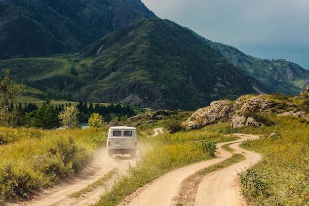 車は山と丘の間の未舗装の道路に沿って前進しています。山アルタイ。