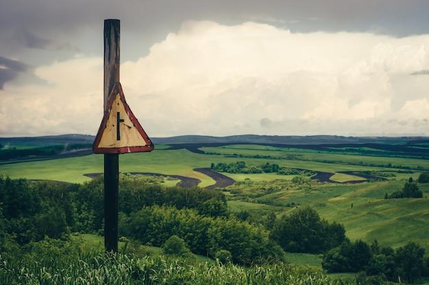 道路と劇的な緑の山の風景は曇り空の下で背景フィールドにサインオンします。