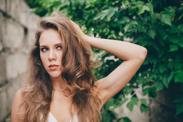 緑の木の近くの白いドレスで自然な巻き毛を持つ美しい気違い女の子を残します