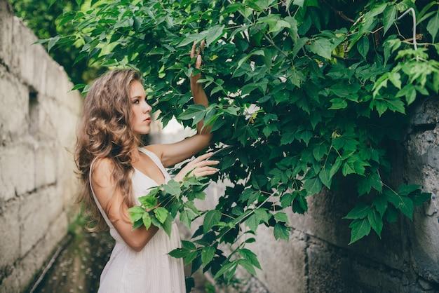 緑の木の近くの白いドレスで自然な巻き毛の美しい幸せな女の子を葉します。