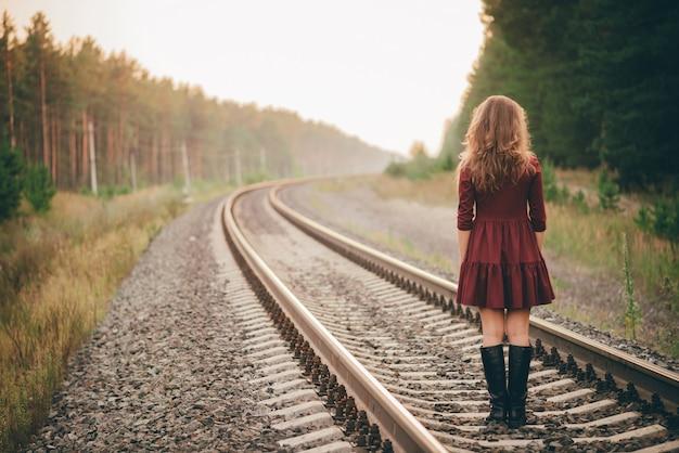 巻き毛の自然な髪の美しいダンス少女は鉄道の森で自然を楽しむ