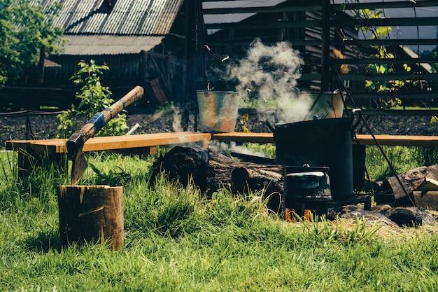 ロシアの国の快適さ切り株の斧。やかんと大きな鍋が絡んでいます。ベンチにバケツします。どこでも芝生。村の家を背景に。