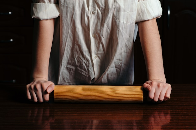 女の子は木製の麺棒を保持しています。