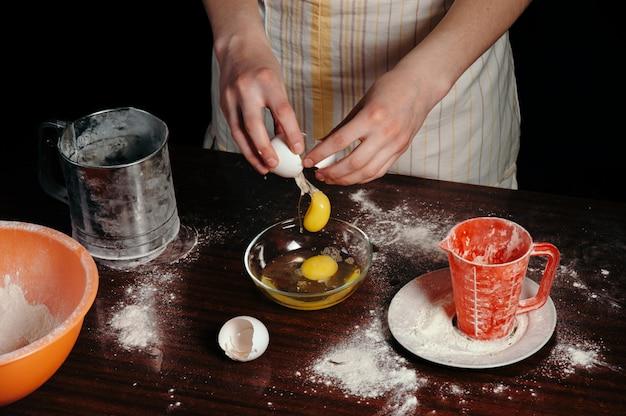暗いキッチンでエプロンの女の子は卵をボウルに分割します。