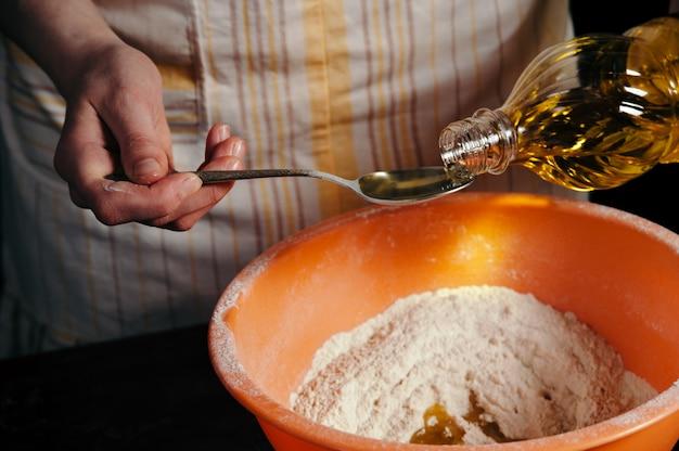 女性の手が小麦粉をボウルにひまわり油を注ぐ
