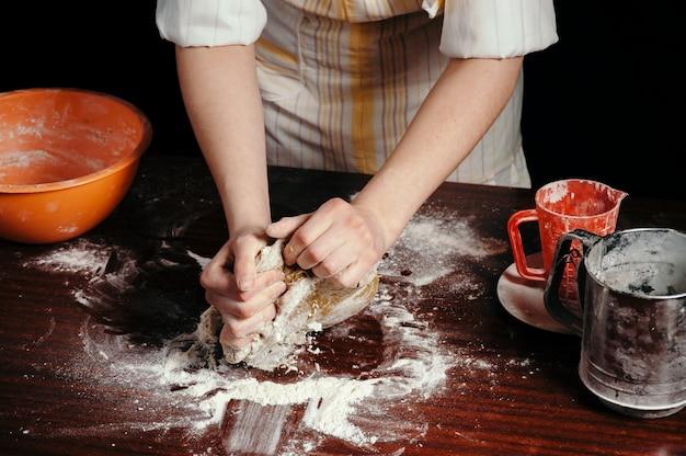 暗いキッチンでエプロンの女の子は、木製キッチンテーブルの上の彼女の手で生地を練ります