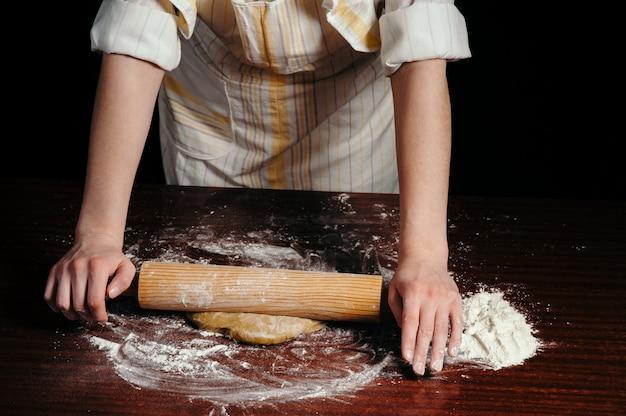 キッチンの女性は、木製の麺棒で木製のテーブルに生地を圧延しています。