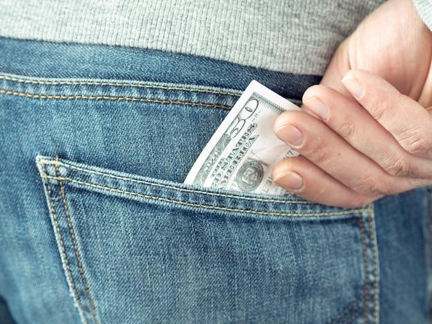 手はジーンズのポケットにドルを入れて