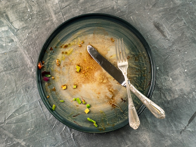 灰色の汚れた皿と銀食器カトラリー