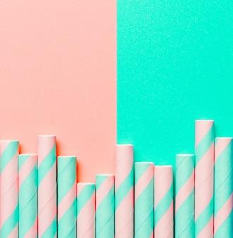 ピンクと青緑色の背景に縞模様の紙ストロー。エコロジー製品。