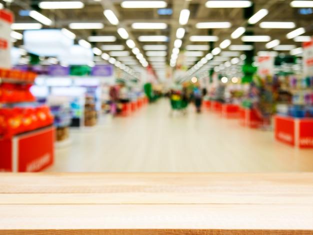 ぼやけているスーパーマーケットの前に木製の空のテーブル