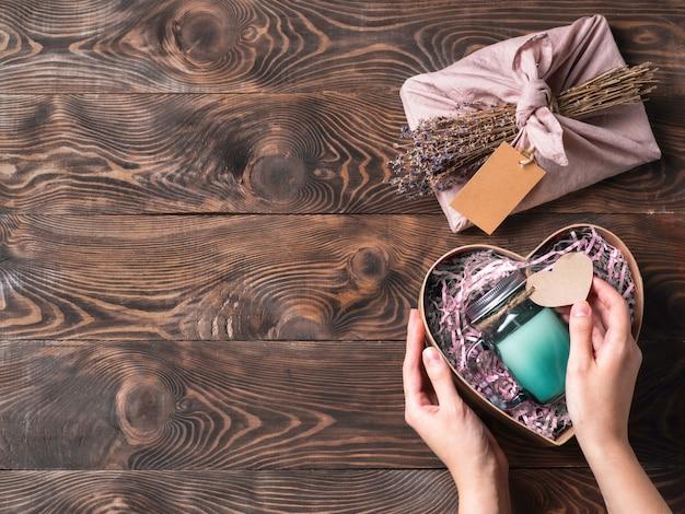 Руки держат подарочную коробку в форме сердца со свечой в стеклянной банке для ноль отходов валентина.