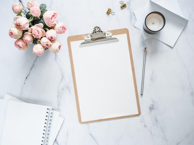 白い空のページを使用してクリップボードの平面図。クリップボード、花、白い大理石の香りキャンドル。