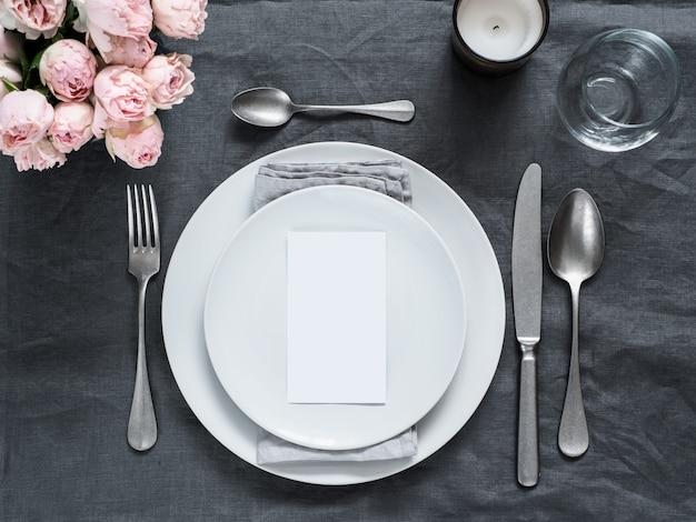 メニュー、結婚式の招待状。グレーのリネンのテーブルクロスに美しいテーブルの設定。