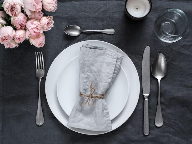 Красивая сервировка стола с розовыми кустовыми розами и свечой на серой льняной скатерти.