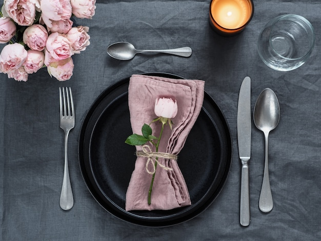 Красивая сервировка стола со свечой на серой льняной скатерти.