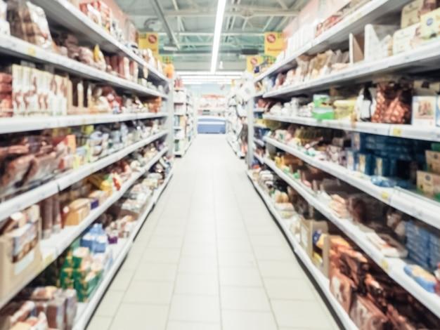 背景としてカラフルな棚と認識できない顧客と抽象的なぼやけたスーパーマーケットの通路