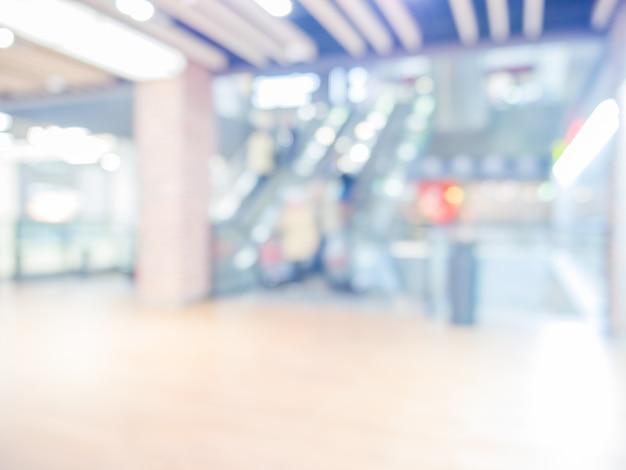 背景としてショッピングモールのぼやけたエスカレーター