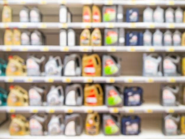 Размытые красочные бутылки моторного масла на полках в супермаркете в качестве фона