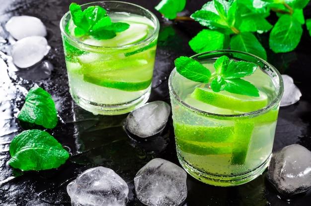 Летний напиток мохито, с лаймом, мятой и кубиками льда, на черном фоне с каплями воды.