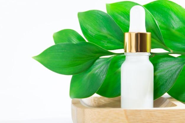 Натуральная косметика: сыворотка с капельницей и зеленые листья на белом фоне.
